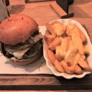 """House Burger"" (AlmOx, Salat, Tomate, Gurke, Swiss Cheese, geb. Champignons & Zwiebel), Cheese-Fries"